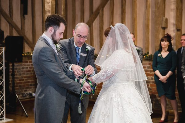 Civil celebrant handfasting a wedding couple